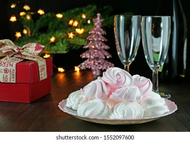 Meringue kisses cookies on plate, gift and champagne glasses on the Christmas table. Christmas tree branches with lights and decorations in the background.