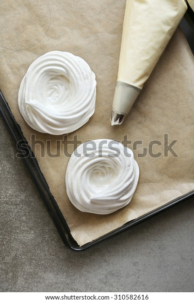 Meringue nests before baking on a tray lined with parchment paper