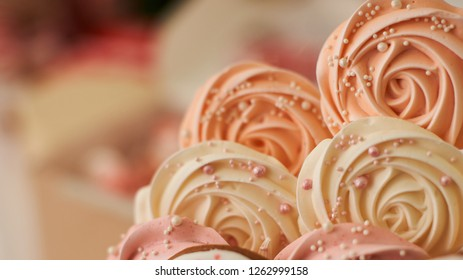 meringue pale pink in the shape of a rose or flower. meringue is a lot of cake decoration, close-up.