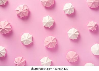 Meringue pattern on pink background. Top view