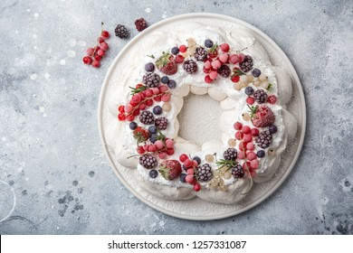 Meringue pavlova wreath cakes with whipped cream and frozen berries, top view, copy space