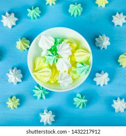 Meringue in a white bowl on a blue  wooden background. Delicious dessert. Colorful handmade meringue.