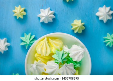 Meringue in a white bowl on a blue  wooden background, top view. Delicious dessert. Colorful handmade meringue.