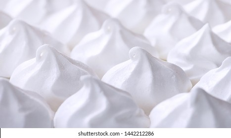 Meringue. White sweet meringue. Tray of meringues. Closeup meringue photo. Dessert background. Sweets. Food.