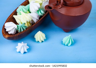 Meringue in a wooden bowl and brown teapot on a blue background. Delicious dessert. Colorful handmade meringue.
