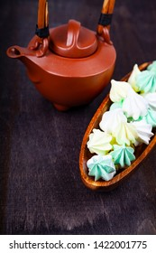 Meringue in a wooden bowl and and brown teapot on a dark background. Delicious dessert. Colorful handmade meringue .