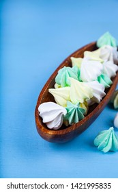 Meringue in a wooden bowl on a blue background. Delicious dessert. Colorful handmade meringue.