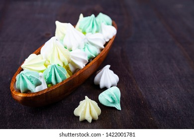 Meringue in a wooden bowl on a dark background. Delicious dessert. Colorful handmade meringue.