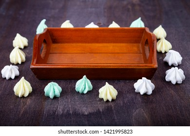 Meringue and a wooden tray on a dark background. Delicious dessert. Colorful handmade meringue.