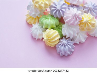Meringues on light pastel background