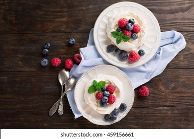Meringues Pavlova cakes with fresh raspberry and blueberry on dark rustic wooden background, top view
