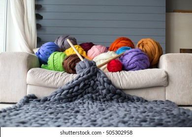 Merino wool balls in multicolour lying on white sofa with merino wool grey blanket with a wooden needles