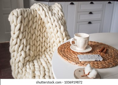Merino wool handmade knitted blanket on a chair in the kitchen
