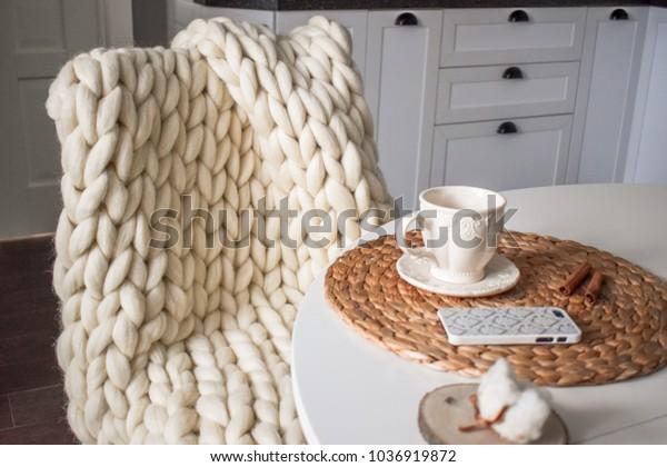 Manta de punto a mano de lana Merino en una silla de la cocina