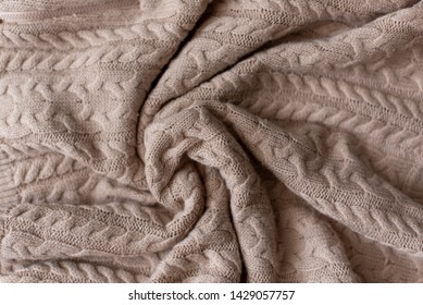 Merino wool handmade knitted large blanket, super chunky yarn, trendy concept. Close-up of knitted blanket, merino wool background. designer blanket made of beige smoky wool