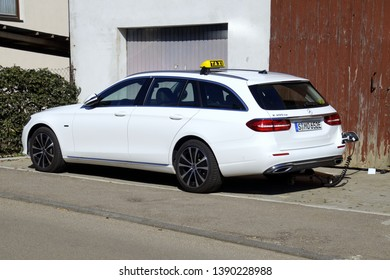Merklingen, Baden-Württemberg, Germany - April 19, 2019: White Mercedes-Benz E 300 DE Plug in hybrid Estate Taxi being charged by the side of the road.