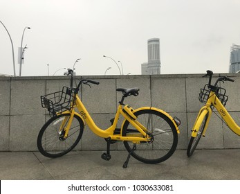 """Merlion Park, Singapore – February 2, 2018: two of rental by application """"ofo"""" brand bicycles parking on bridge in front of Merlion Park, Singapore"""