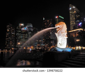 .Merlion from Singapore.  Singapore, Singapore - June 5, 2016 Merlion, gushing with water in the evening scenery, against the background of skyscrapers at Merlion Park in Singapore.