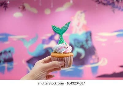 Mermaid cupcake. A lady's hand holding a mermaid buttercream cupcake with soft focus on the green fish tail.