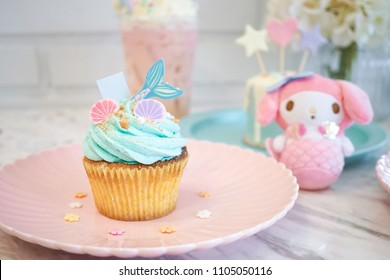 Mermaid cupcake. A mermaid muffin against the white brick wall background and a cute mermaid plush animal. fairy tales and fantasy concept. Selective focus on the pink seashell.