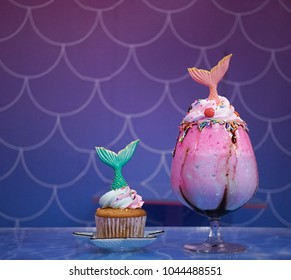 Mermaid cupcake and mermaid rainbow milkshake. With soft focus on the green fish tail in the cupcake. fairy takes and fantasy concept.