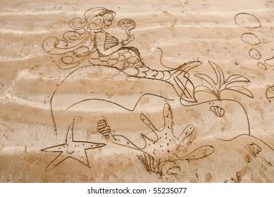 A mermaid drawn on a sandy beach