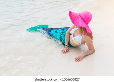 Mermaid girl with glitter green tail put feet in water.  Blonde beautiful Mermaid. Tourist dress up as mermaid travel at the sea. vacation concept. The real mermaid is resting on the beach.