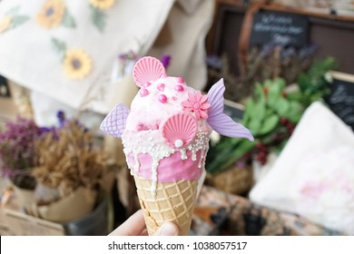 Mermaid ice cream. A very cute strawberry cheesecake ice-cream cone with mermaid inspiration. Mermaid and fairy tales concept. soft focus on the pink flower.