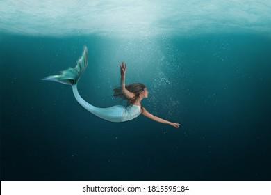 Mermaid swimming under the deep waters of the ocean.