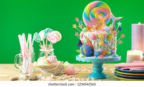 Mermaid theme candyland cake with colorful glitter tails, shells and sea creatures toppers for children's, teen's, novelty birthday and party celebrations, green background.
