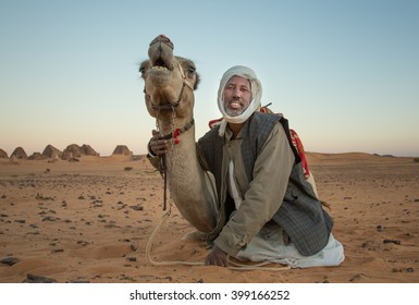 MEROE PYRAMIDS, SUDAN - CIRCA DECEMBER 2015: a man posing with a camel with Meroe pyramids at the background