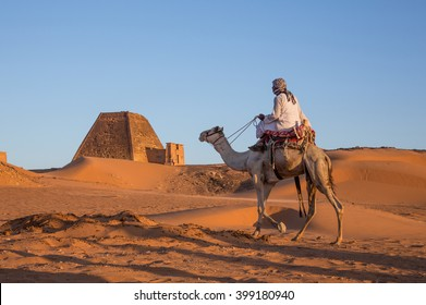 MEROE PYRAMIDS, SUDAN - CIRCA DECEMBER 2015: man on a camel in a desert with pyramid behind him