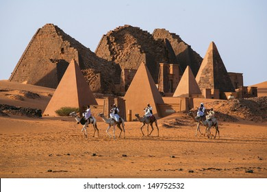MEROE PYRAMIDS, SUDAN - NOV 02 : Unidentified Sudanese bedouins ride camels with the famous Meroe pyramids of the ancient Nubian city in the background, on November 02, 2007 in Sudan