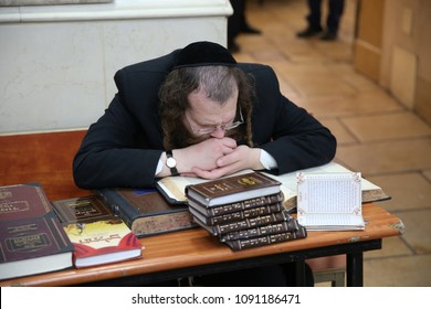 MERON, ISRAEL - APR 29, 2018: An unidentified orthodox Jewish man in a black suit and sidelocks, learns Torah books at a desk in Meron, Israel