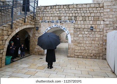 MERON, ISRAEL - APRIL 28, 2018: An unidentified orthodox Jew walks through the entrance to the grave of Rabbi Shimon Bar Yochai holding an umbrella in Meron, Israel