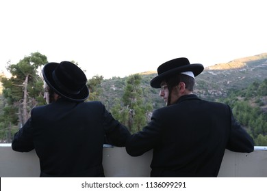 MERON, ISRAEL - AUG 1, 2017: Unidentified orthodox Jewish youth stand leaning on a wall and looking at the view in Meron, Israel