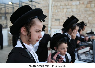 MERON, ISRAEL - AUG 2, 2018: Unidentified hasidic Jewish teenagers pray at the grave of Rabbi Shimon Bar Yochai the morning service in Meron, Israel while donning leather straps called Tefillin