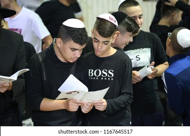 MERON, ISRAEL - AUG 26, 2018: Unidentified non religious Jewish teenagers are lead by their Rabbi teacher in saying the forgiveness prayer at the grave of Rabbi Shimon Bar Yochai in Meron, Israel