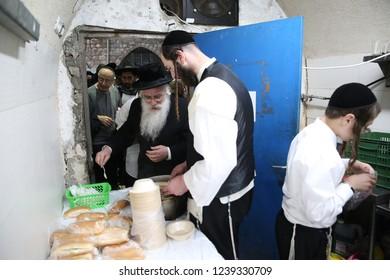 "MERON, ISRAEL - DEC 20, 2017: Rabbi Shraga Shnitzer of the volunteer organization ""Ohel Rashbi"" serves free food to people visiting the tomb of Rabbi Shimon Bary Yochai in Meron, Israel"