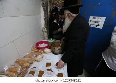 "MERON, ISRAEL - DEC 20, 2017: Rabbi Shraga Shnitzer of the volunteer organization ""Ohel Rashbi"" serves free food to people visiting the tomb of Rabbi Shimon Bar Yochai in Meron, Israel"