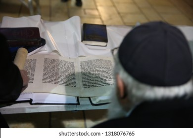 "MERON, ISRAEL - FEB 28, 2018: Unidentified orthodox Jewish Rabbi and sage reads the ""Megillah"" (scroll of Esther), a Jewish text read on the holiday of Purim in Meron, Israel"