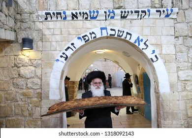 "MERON, ISRAEL - FEB 28, 2018: Rabbi Shraga Shnitzer of the charity called ""Ohel Rashbi"", carries a huge challah bread baked in honor of the Jewish holiday of Purim in Meron, Israel"