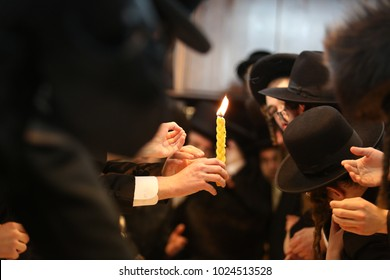"MERON, ISRAEL - FEB 3, 2018: Orthodox religious hasidic jews extend their hands to the light of the ""Havdalah"" candle. ""Havdalah"" is a Jewish ritual separating the holy Shabbat and weekday"