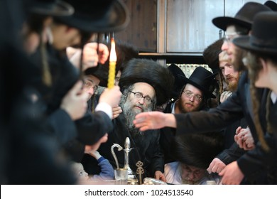 """MERON, ISRAEL - FEB 3, 2018: Orthodox religious hasidic jews extend their hands to the light of the """"Havdalah"""" candle. """"Havdalah"""" is a Jewish ritual separating the holy Shabbat and weekday"""
