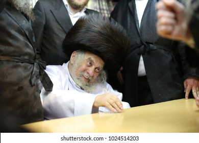 """MERON, ISRAEL - FEB 3, 2018: Rabbi Yechezkel Roth extends his hands to the light of the """"Havdalah"""" candle. """"Havdalah"""" is a Jewish ritual separating the holy Shabbat and weekday"""