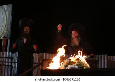 MERON, ISRAEL - MAY 14, 2017: Rabbi Chaim Shmeler, head of the Yeshiva Orayta school, lights bonfire in on the Lag Baomer holiday at the grave of Rabbi Shimon Bar Yochai in Meron, Israel