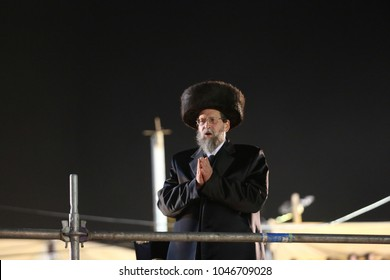 "MERON, ISRAEL - MAY 14, 2017: Jewish Grand Rabbi of Boyan hasidic sect prays and lights bonfire at the grave of Rabbi Shimon bar Yochai on the Jewish holiday of ""Lag Baomer"" in Meron, Israel"