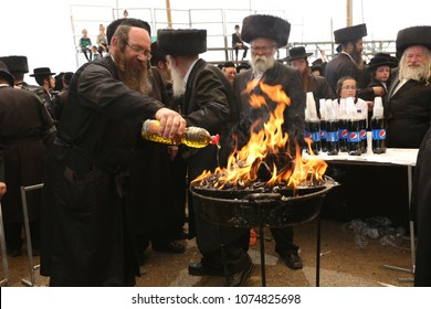 MERON, ISRAEL - MAY 14, 2017: Unidentified hasidic Rabbi pours oil from a bottle onto bonfire lit in honor of Rabbi Shimon Bar Yochai on the Jewish holiday of Lag Baomer in Meron, Israel