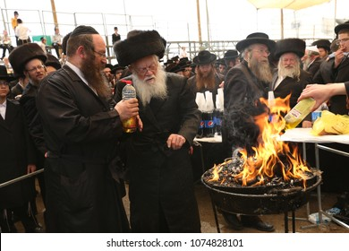 MERON, ISRAEL - MAY 14, 2017: Unidentified hasidic Rabbis watch blaze while holding oil bottle by bonfire lit in honor of Rabbi Shimon Bar Yochai on the Jewish holiday of Lag Baomer in Meron, Israel