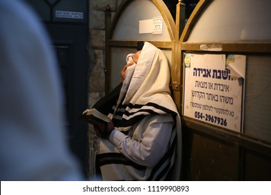 MERON, ISRAEL - MAY 29, 2018: Unidentified Jewish man covers his eyes in prayer while wearing a prayer shawl at the grave of Rabbi Shimon Bar Yochai at sunrise in Meron, Israel
